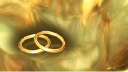 Royalty Free Video of Rotating Wedding Rings With a Gold Shimmery Background