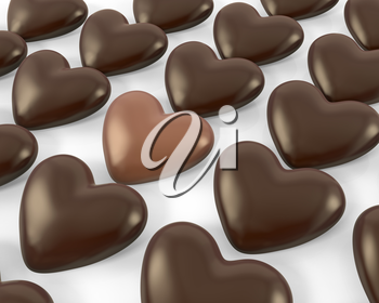 Heart shaped milk chocolate candy between dark ones, isolated on white background