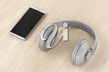 Big wireless headphones and smartphone on wood table