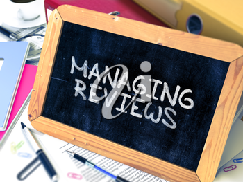 Managing Reviews Handwritten by White Chalk on a Blackboard. Composition with Small Chalkboard on Background of Working Table with Office Folders, Stationery, Reports. Blurred, Toned 3d Image.