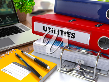 Red Ring Binder with Inscription Utilities on Background of Working Table with Office Supplies, Laptop, Reports. Toned Illustration. Business Concept on Blurred Background. 3D Render.