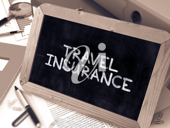 Travel Insurance Handwritten on Chalkboard. Composition with Small Chalkboard on Background of Working Table with Ring Binders, Office Supplies, Reports. Blurred Background. Toned Image. 3D Render.