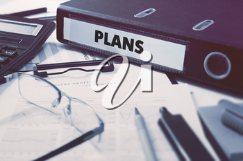Plans - Office Folder on Background of Working Table with Stationery, Glasses, Reports. Business Concept on Blurred Background. Toned Image.