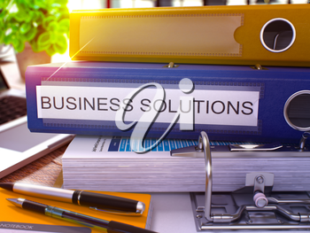 Blue Ring Binder with Inscription Business Solutions on Background of Working Table with Office Supplies and Laptop. Business Solutions Business Concept on Blurred Background. 3D Render.