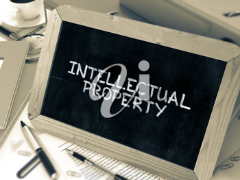 Intellectual Property Handwritten on Chalkboard. Composition with Small Chalkboard on Background of Working Table with Ring Binders, Office Supplies, Reports. Blurred, Toned Image. 3D Render.