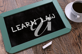 Learn Law Handwritten on Blue Chalkboard. Business Concept. Composition with Chalkboard and Cup of Coffee. Top View Image. 3D Render.