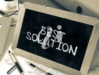 Best Solution Handwritten by White Chalk on a Blackboard. Composition with Small Chalkboard on Background of Working Table with Office Folders, Stationery, Reports. Blurred, Toned Image. 3D Render.