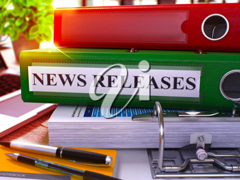 Green Ring Binder with Inscription News Releases on Background of Working Table with Office Supplies and Laptop. News Releases Business Concept on Blurred Background. 3D Render.