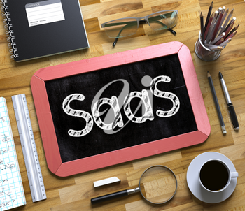 Small Chalkboard with SaaS. SaaS - Red Small Chalkboard with Hand Drawn Text and Stationery on Office Desk. Top View. 3d Rendering.