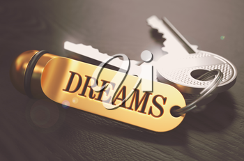 Dreams - Concept on Golden Keychain over Black Wooden Background. Closeup View, Selective Focus, 3D Render. Toned Image.
