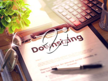 Downsizing- Text on Clipboard with Office Supplies on Desk. 3d Rendering. Blurred Illustration.