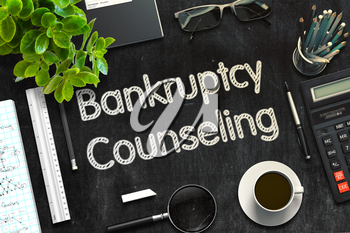 Black Chalkboard with Handwritten Business Concept - Bankruptcy Counseling - on Black Office Desk and Other Office Supplies Around. Top View. 3d Rendering. Toned Illustration.