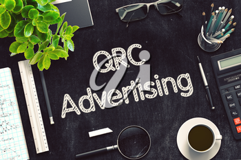 QRC Advertising. Business Concept Handwritten on Black Chalkboard. Top View Composition with Chalkboard and Office Supplies. 3d Rendering. Toned Image.