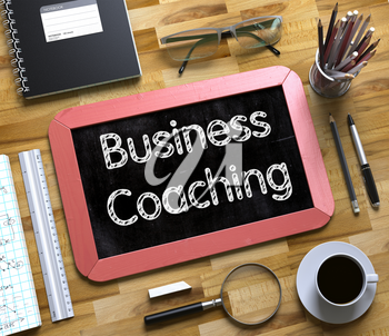 Business Coaching Concept on Small Chalkboard. Red Small Chalkboard with Handwritten Business Concept - Business Coaching - on Office Desk and Other Office Supplies Around. Top View. 3d Rendering.