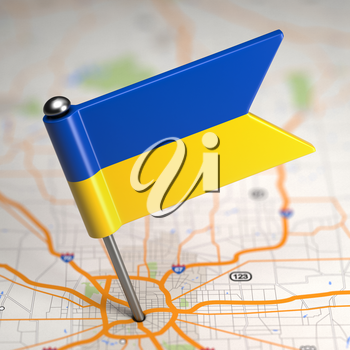 Small Flag of Ukraine Sticked in the Map Background with Selective Focus.