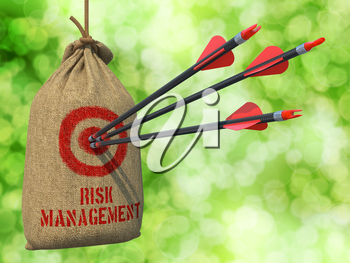Risk Management - Three Arrows Hit in Red Target on a Hanging Sack on Green Bokeh Background.