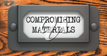 Compromising Materials - Inscription on File Drawer Label on a Wooden Background.