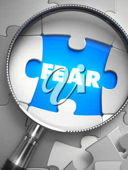 Fear - Word on the Place of Missing Puzzle Piece through Magnifier. Selective Focus.