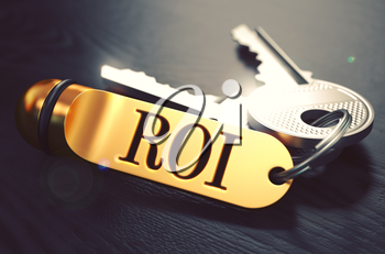 Keys and Golden Keyring with the Word ROI - Return On Investment - over Black Wooden Table with Blur Effect. Toned Image.