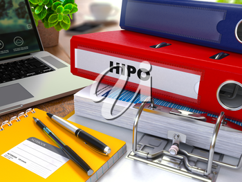 Red Ring Binder with Inscription HiPo on Background of Working Table with Office Supplies, Laptop, Reports. Toned Illustration. Business Concept on Blurred Background.