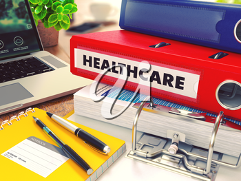 Healthcare - Red Office Folder on Background of Working Table with Stationery, Laptop and Reports. Business Concept on Blurred Background. Toned Image.
