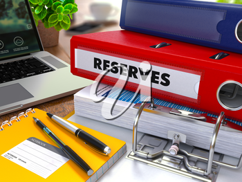 Red Ring Binder with Inscription Reserves on Background of Working Table with Office Supplies, Laptop, Reports. Toned Illustration. Business Concept on Blurred Background.