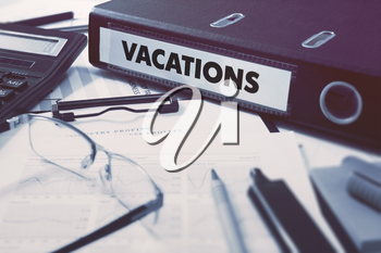 Vacations - Office Folder on Background of Working Table with Stationery, Glasses, Reports. Business Concept on Blurred Background. Toned Image.