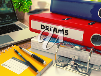 Red Office Folder with Inscription Dreams on Office Desktop with Office Supplies and Modern Laptop. Business Concept on Blurred Background. Toned Image.