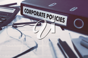 Corporate Policies - Office Folder on Background of Working Table with Stationery, Glasses, Reports. Business Concept on Blurred Background. Toned Image.
