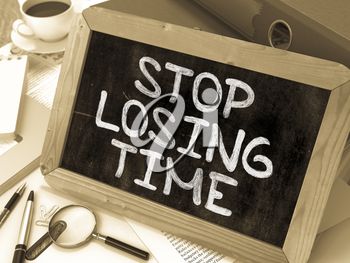 Stop Losing Time. Motivational Quote Handwritten on Chalkboard. Composition with Small Chalkboard on Background of Working Table with Ring Binders, Office Supplies, Reports. Blurred Background. Toned