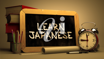 Learn Japanese Handwritten by white Chalk on a Blackboard. Composition with Small Chalkboard and Stack of Books, Alarm Clock and Rolls of Paper on Blurred Background. Toned Image.