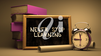 Never Stop Learning Handwritten by white Chalk on a Blackboard. Composition with Small Chalkboard and Stack of Books, Alarm Clock and Rolls of Paper on Blurred Background. Toned Image.