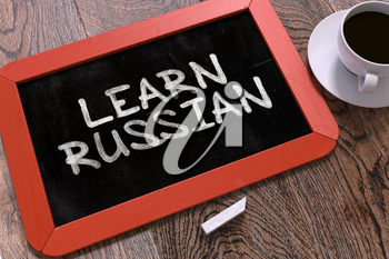 Learn Russian Handwritten by white Chalk on a Blackboard. Composition with Small Red Chalkboard and Cup of Coffee. Top View.