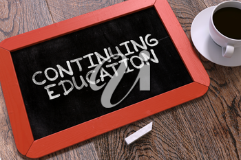 Continuing Education Concept Hand Drawn on Red Chalkboard on Wooden Table. Educational Background. Top View.