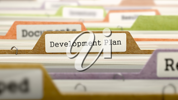 Development Plan on Business Folder in Multicolor Card Index. Closeup View. Blurred Image.