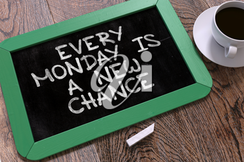 Every Monday is a New Chance. Inspirational Quote Hand Drawn on Green Chalkboard on Wooden Table. Business Background. Top View.