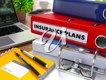 Red Ring Binder with Inscription Insurance Plans on Background of Working Table with Office Supplies, Laptop, Reports. Toned Illustration. Business Concept on Blurred Background.