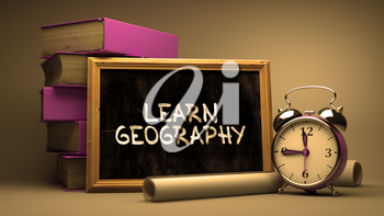 Learn Geography - Chalkboard with Hand Drawn Inspirational Quote, Stack of Books, Alarm Clock and Rolls of Paper on Blurred Background. Toned Image.