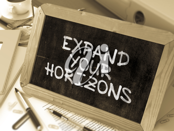 Expand Your Horizons. Motivation Quote on a Blackboard. Composition with Small Chalkboard on Background of Working Table with Office Folders, Stationery, Reports. Blurred, Toned Image.