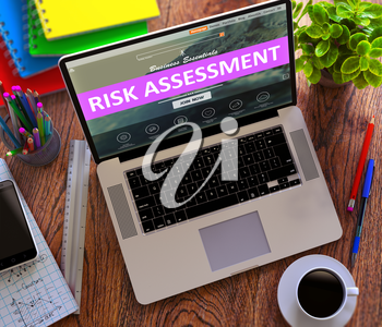 Risk Assessment Concept. Modern Laptop and Different Office Supply on Wooden Desktop background.
