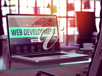 Web Development Concept. Closeup Landing Page on Laptop Screen  on background of Comfortable Working Place in Modern Office. Blurred, Toned Image.