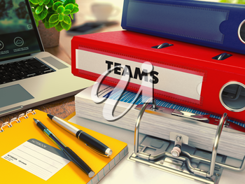 Red Office Folder with Inscription Teams on Office Desktop with Office Supplies and Modern Laptop. Business Concept on Blurred Background. Toned Image.