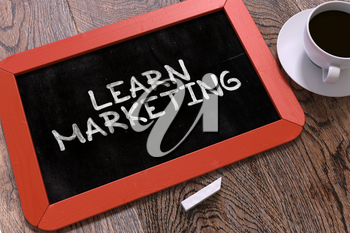 Learn Marketing Handwritten by white Chalk on a Blackboard. Composition with Small Red Chalkboard and Cup of Coffee. Top View. 3d Illustration.