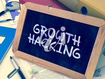 Handwritten Growth Hacking on a Chalkboard. Composition with Chalkboard and Ring Binders, Office Supplies, Reports on Blurred Background. Toned 3d Image.