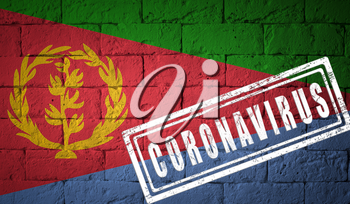 Flag of the Eritrea on brick wall texture. stamped of Coronavirus. Corona virus concept. On the verge of a COVID-19 or 2019-nCoV Pandemic. Novel Chinese Coronavirus outbreak