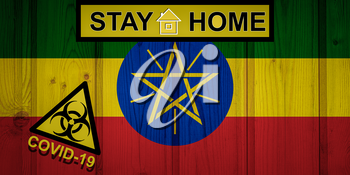 Flag of the Ethiopia in original proportions. Quarantine and isolation - Stay at home. flag with biohazard symbol and inscription COVID-19.