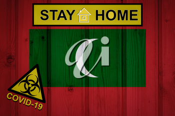 Flag of the Maldives in original proportions. Quarantine and isolation - Stay at home. flag with biohazard symbol and inscription COVID-19.