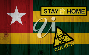 Flag of the Togo in original proportions. Quarantine and isolation - Stay at home. flag with biohazard symbol and inscription COVID-19.